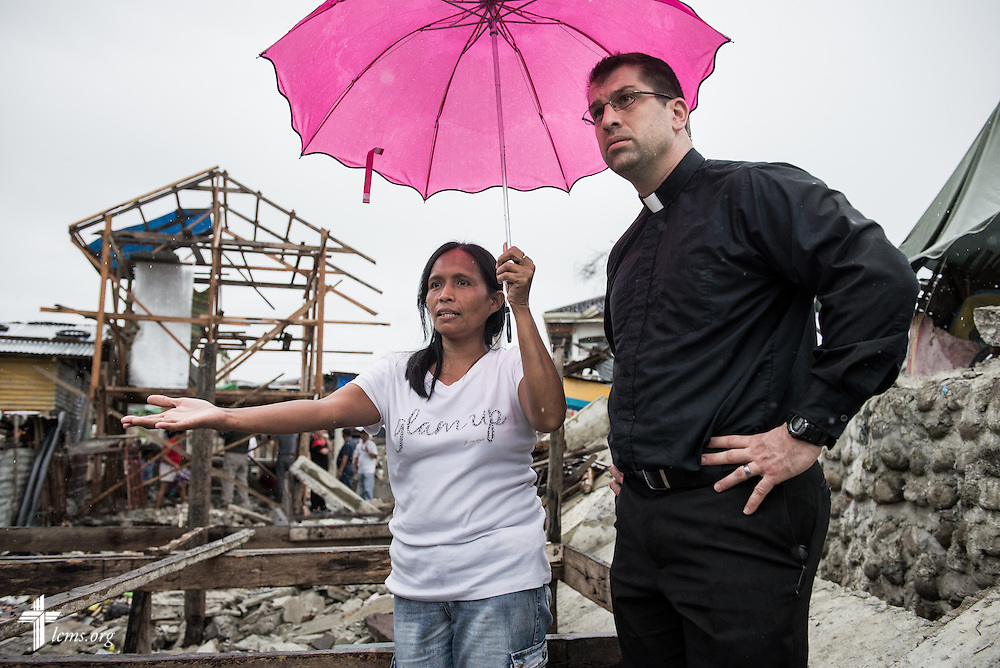 A member of Christ Lutheran Church affected by Typhoon Haiyan shows devastation in her neighborhood to the Rev. Ross Johnson, director of LCMS Disaster Response, in Tacloban, Leyte Province, Philippines, on Friday, March 14, 2014. LCMS Communications/Erik M. Lunsford
