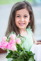 Portrait of smiling girl holding roses and gift box at home