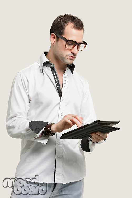 Young man using digital tablet against gray background