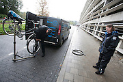 In de stromende regen repareert een mobiele fietsenmaker een fiets, vlakbij het transferium Westraven in Utrecht.<br /> <br /> A mechanic of a mobile bike repair is repairing a bike with a flat tyre nearby a transferium in Utrecht.