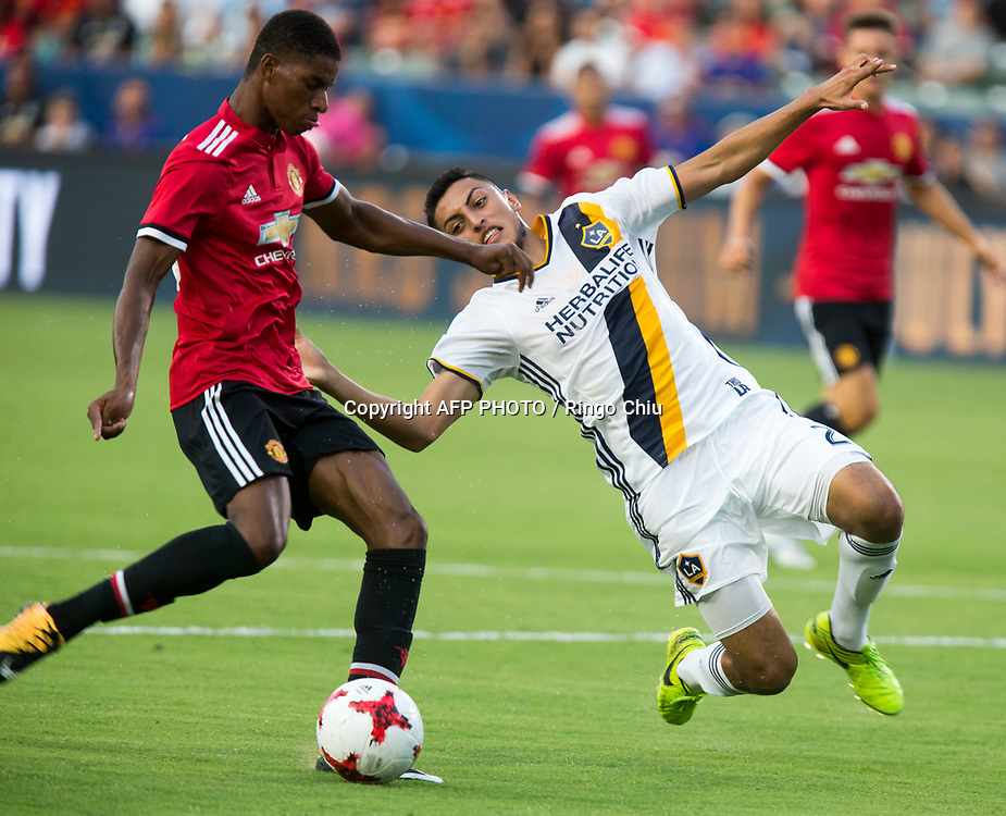 Manchester United Marcus Rashford, left, kicks the ball against Los Angeles Galaxy during the first half of a national friendly soccer game at StubHub Center on July 15, 2017 in Carson, California.   AFP PHOTO / Ringo Chiu