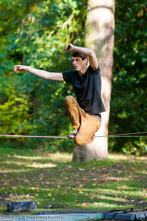 Slack Wire or slack rope walker practises on a rope fixed between two trees in Endcliffe Park Sheffield<br />