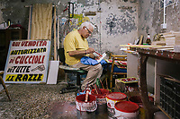 NAPLES, ITALY - 13 JULY 2017:  Pasquale O' Nummanaro (Pasquale The Number Man) makes hand made signs used by food businesses and fruit and vegetable vendors all over Naples are seen here in his workshop in Naples, Italy, on July 13th 2017.