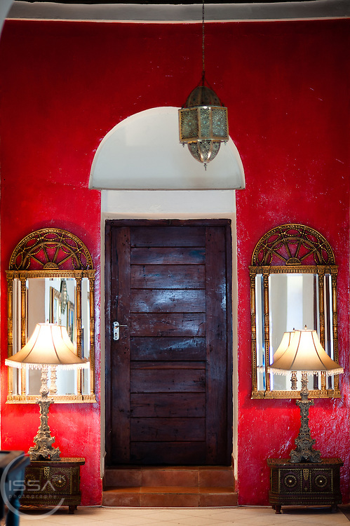 Red wall. Two lamps and a wooden door