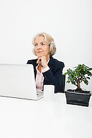 Thoughtful senior businesswoman with laptop sitting at desk in office