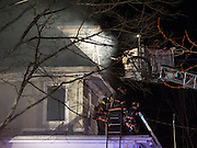 Chappaqua, NY - April 11, 2014: Firefighters from Chappaqua and several surrounding towns in Westchester County New York fight a blaze in a building that houses the Whispering Pines Flower Shop and residential apartments in Chappaqua, NY. The fire began around 1 AM Friday morning and as of 5:30 AM the fire was still going, with heavy smoke blanketing the surrounding area. © 2014 Marianne A. Campolongo