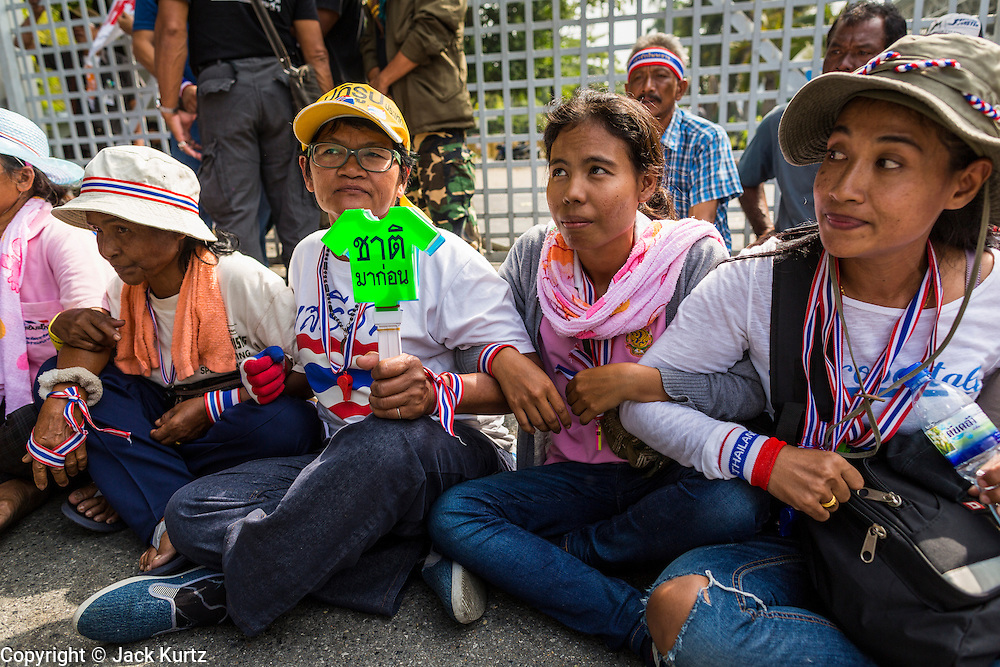 24 DECEMBER 2013 - BANGKOK, THAILAND: Women sit on the ground in front of the gates to the Thai-Japan Stadium to block access to the stadium during a protest Wednesday. Hundreds of anti-government protestors are camped out around the Thai-Japan Stadium in Bangkok, where political parties are supposed to register for the election on February 2. As of Dec 24, nine of the more than 30 parties were able to register. Protestors hope to prevent the election. The action is a part of the ongoing protests in Bangkok that have caused the dissolution of the elected government.      PHOTO BY JACK KURTZ