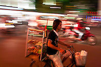 Street vendors riding around the bustling city of Saigon.