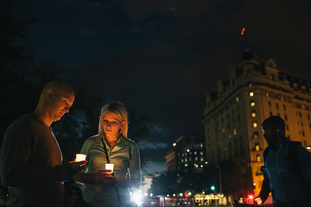 WASHINGTON, DC - SEPTEMBER 16:  Dave Gray and wife Brittany, of Salt Lake City, hold candles in remembrance of people affected by gun violence during a vigil at Freedom Plaza in Washington, D.C. on Sept. 16, 2013. The vigil, during which organizers called for stricter gun laws, was in remembrance of the more than 10 killed in a shooting at the Navy Yard earlier in the day.   (Photo by Greg Kahn/Getty Images)