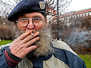 Homeless man smoking a cigarette in a park beside Malostranska subway where he lives on a bench almost the whole year.