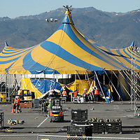 The Crew from Cirque du Soleil begin to raise part of the blue and yellow Grand Chapiteau (Big Top) at the Santa Monica Pier on Monday, January 9, 2012.<br /> <br /> The Grand Chapiteau will stand 66 feet high and is 167 feet in diameter. The 4 masts stand at 80 feet tall each. 550 pegs are required to hold the Grand Chapiteau firmly to the 4,500 square metres of asphalt. The Grand Chapiteau can accommodate more than 2,500 people. The entire site set-up takes 7 days. This includes installation of entrance, hospitality and rehearsal tents, box office, administrative offices and kitchen.<br /> <br /> The Grand Chapiteau, the Tapis Rouge and Artistic tents are all climate controlled with air conditioning in warm seasons or heating for colder seasons. The Grand Chapiteau travels via 61 trailers carrying more than 1,000 tons of equipment for the tour.