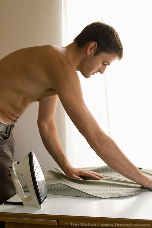 A young caucasian man irons his shirt.