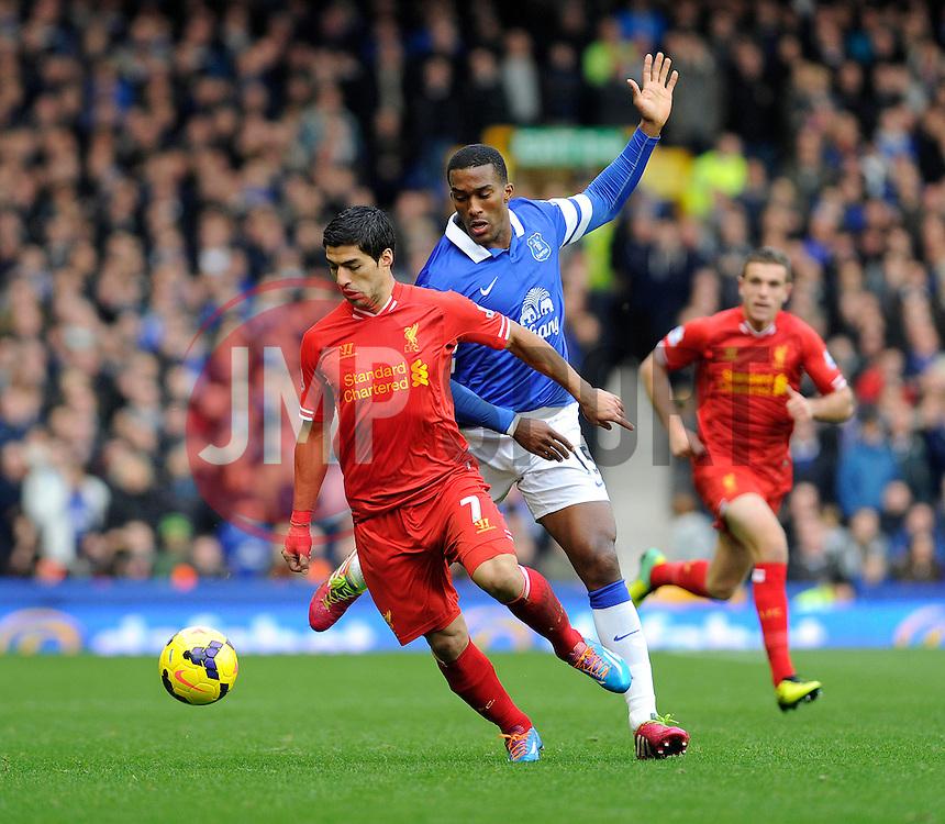 Liverpool's Luis Suarez controls the ball under pressure from Everton's Sylvain Distin - Photo mandatory by-line: Dougie Allward/JMP - Tel: Mobile: 07966 386802 23/11/2013 - SPORT - Football - Liverpool - Merseyside derby - Goodison Park - Everton v Liverpool - Barclays Premier League