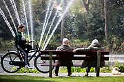 In Zeist zitten twee oudere mensen met hun hondje in het park op een bankje. Een jongen passeert op de fiets met een voetbal.<br /> <br /> In Zeist two older people sit with their dog on a bench in a park. A boy passes on a bike.