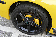 Bellmore, New York, USA. 12th June 2015. A rear wheel tire closeup of a modified yellow 2003 Corvette 50th Anniversary model, an award winning car owned by Grey Cherveny of Bay Shore, is displayed  at the Friday Night Car Show held at the Bellmore Long Island Railroad Station Parking Lot. Hundreds of classic, antique, and custom cars were on view at the free weekly show, sponsored by the Chamber of Commerce of the Bellmores.