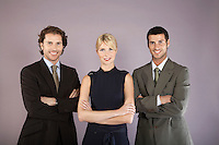Three business people with arms crossed portrait