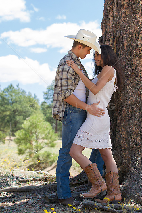 sexy cowboy couple embracing while standing outdoors under a tree in New Mexico