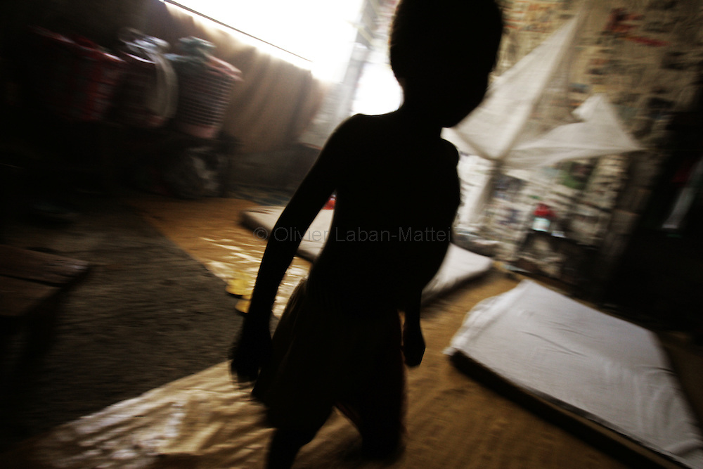 """Photo taken 19 September 2005 of a child inside the former uncompleted Ministry of National Defense building in Congo Town on the outskirts of Monrovia. The """"Pentagon"""", named this way by its occupants, shelters 394 families totalling approximately 3,000 people who were booted out in May 2005 of the Barclay Training Center, which had been their home for the last two decades. Former soldiers, who fought for former Liberian presidents Samuel Doe and Charles Taylor, live in this building with no water or electricity, overcoming past differences. The construction of the building started in 1984 under Doe's leadership, and the war interrupted the its completion and later served as a base for Taylor's men."""