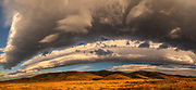 Dawn cloudscape arches over tussock grass covered hills, St Bathans, Central Otago, New Zealand.