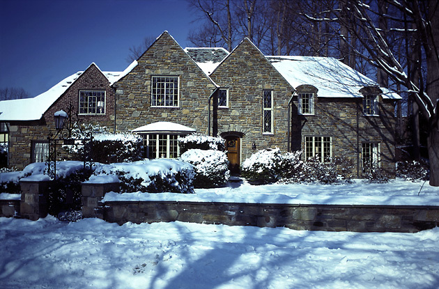 stone Tudor style house, snow; casement windows; slate roof, iron gate; low stone wall; winter