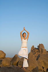 Jul. 26, 2012 - Woman in yoga pose by rocks (Credit Image: © Image Source/ZUMAPRESS.com)