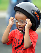 A boy named A, three years old, puts a helmet on during a Moving in Peace motorcade thru all of Camden's neighborhoods to recognize and honor the victims of violence in the city Saturday, August 12, 2017 at Farnham Park in Camden, New Jersey. (Photo by William Thomas Cain)(WILLIAM THOMAS CAIN / For The Philadelphia Inquirer)