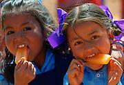 Nepalese girls (possibly sisters) enjoying orange ice lollies in rural Nepal.