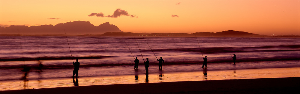 Men fishing on The Strand beach at sunset