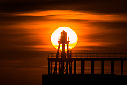 © Licensed to London News Pictures. 26/04/2018. Whitby UK. Picture shows the sun rising this morning behind the lighthouse at the end of Whitby pier on the Yorkshire coast. Photo credit: Andrew McCaren/LNP