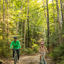 A woman and her daughter ride bikes near Deboullie Pond in Aroostook County, Maine. Deboullie Public Reserve Land.