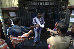 November 13, 2016 - Kolkata, West Bengal, India - Bank employee distribute exhange froms to the people in front of a bank. To facilitate smooth exchange and deposit the old Rs. 500 and Rs. 1000 bank note bank across India remain open for public on Sunday , as announced by Union Government after demonetized Rs.500 and Rs.1000 bank notes to tackle the menace of black money. Indian line up outside the banks to deposit and exchange demonetized bank note from late night. (Credit Image: © Saikat Paul/Pacific Press via ZUMA Wire)