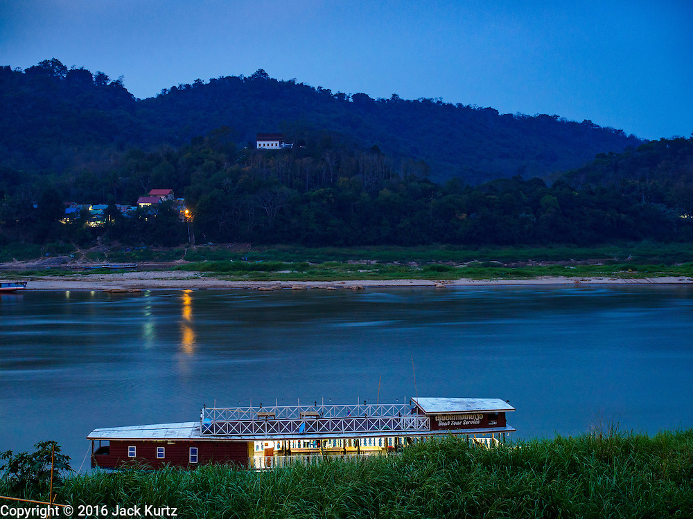"12 MARCH 2016 - LUANG PRABANG, LAOS:  A tourist cruise boat parked on the banks of the Mekong River in Luang Prabang. Luang Prabang was named a UNESCO World Heritage Site in 1995. The move saved the city's colonial architecture but the explosion of mass tourism has taken a toll on the city's soul. According to one recent study, a small plot of land that sold for $8,000 three years ago now goes for $120,000. Many longtime residents are selling their homes and moving to small developments around the city. The old homes are then converted to guesthouses, restaurants and spas. The city is famous for the morning ""tak bat,"" or monks' morning alms rounds. Every morning hundreds of Buddhist monks come out before dawn and walk in a silent procession through the city accepting alms from residents. Now, most of the people presenting alms to the monks are tourists, since so many Lao people have moved outside of the city center. About 50,000 people are thought to live in the Luang Prabang area, the city received more than 530,000 tourists in 2014.      PHOTO BY JACK KURTZ"