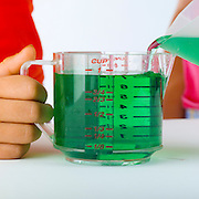 Volumes of liquid being measured by girls in a graduated cylinder.