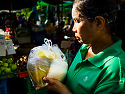 20 JUNE 2018 - BANGKOK, THAILAND: A woman with packaged food in plastic bags at Makkasan Market, a small local market in central Bangkok. Officials in Thailand are wrestling with Thais use of plastic bags. The issue became a public one in early June when a whale in Thai waters died after ingesting 18 pounds of plastic. In a recent report, Ocean Conservancy claimed that Thailand, China, Indonesia, the Philippines, and Vietnam were responsible for as much as 60 percent of the plastic waste in the world's oceans.     PHOTO BY JACK KURTZ