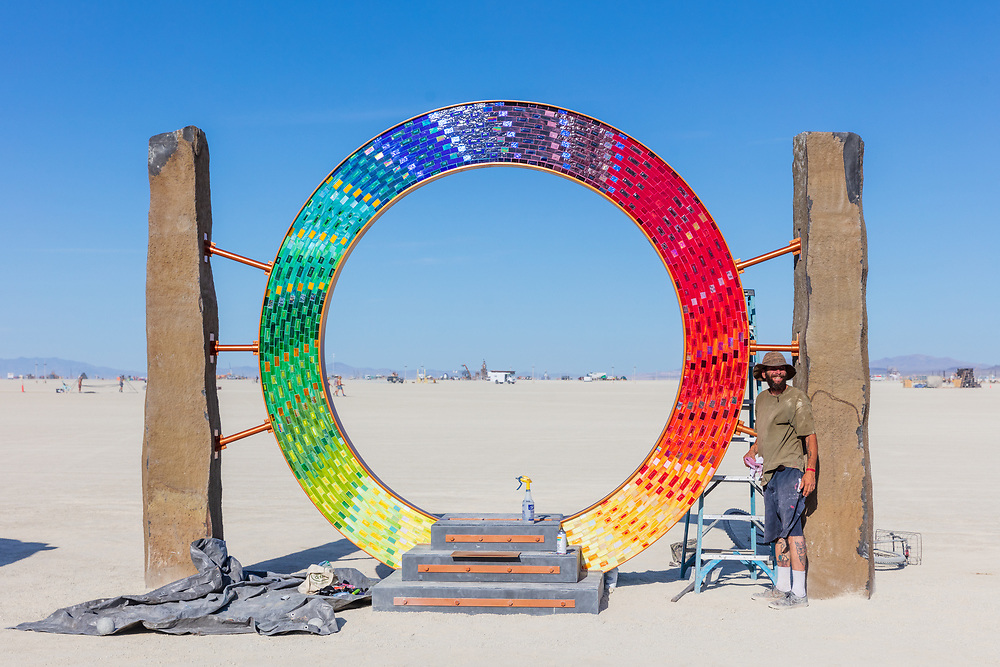 "Portal Build<br /> by: David Oliver and the Art City Monsters<br /> from: Ventura, CA<br /> year: 2019<br /> <br /> A Portal possible of transformation… not to that which is coming, but to things here. With a ring 12′ in diameter made from 4,608 stained glass tiles with a total of 24 colors, graduating the color wheel in a flowing mosaic that is two sided. Two 7-thousand-pound basalt stone columns stand guard from the left and from the right. Portal will also be lit with an increasing laser light show controlled on a theremin device, with sound effects that go off when one enters.<br /> <br /> Symbiosis.<br /> <br /> The color in harmony attracts vitality through beauty, like a flower does a bee. The bee gets food in exchange for spreading pollen. In the same manner one attracts to Portal. Coming out with powerful frequencies, to bounce off their friends, their family, the animals, EARTH, and even so called… ""enemies.""<br /> <br /> URL: http://www.facebook.com/PORTALbrc/<br /> <br /> https://burningman.org/event/brc/2019-art-installations/?yyyy=&artType=H#a2I0V000001AVueUAG"