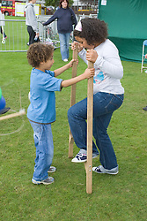 Boy helping to hold steady stilts for sister at a Parklife summer activities event,