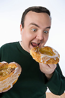 Overweight mid-adult man eating pastry