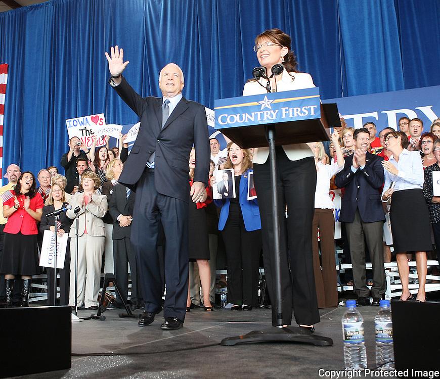 US Republican presidential nominee Senator John McCain (R-AZ)  waves to the crowd as his running mate Alaska Governor Sarah Palin speaks at a campaign rally in Cedar Rapids, Iowa, September 18, 2008.