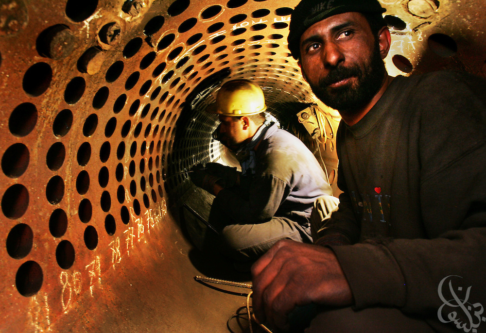 Iraqi workers  from the Power Engineering World Ltd. Company, an Iraqi contracting company work to refurbish super coils inside boiler unit #5 at the Rasheed electric power plant in South Baghdad, Iraq April 7, 2005.