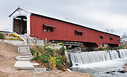 """Bridgeton Historic District, Indiana: Bridgeton Covered Bridge (245 feet long) was rebuilt in historically accurate Burr Arch style in 2006 over Big Raccoon Creek (replacing 1868 bridge burnt by arson in 2005) on Bridgeton Road, Parke County, Indiana, USA. Bridgeton Mill was established 1823, rebuilt 1870, and is the oldest continuously operating mill west of the Allegheny Mountains. The mill grinds wheat into flour and corn into meal with 200 year-old French Buhr stones. Dam and spillway. Red and white paint protects the wood. The traditional """"Cross this bridge at a walk"""" sign required slow vehicle speed, but traffic is now diverted to an adjacent modern bridge."""