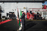 "VALLETTA, MALTA - 8 FEBRUARY 2017:  An official of the Italian Navy holds the Libyan flag on the deck of the San Giorgio, an amphibious transport dock of the Italian Navy, before the graduation ceremony of the first training package of the Libyan Navy Coastguard and Libyan Navy  in Valetta, Malta, on Febuary 8th 2017.<br /> <br /> As a consequence of the April 2015 Libya migrant shipwrecks, the EU launched a military operation known as European Union Naval Force Mediterranean (EUNAVFOR Med), also known as Operation Sophia, with the aim of neutralising established refugee smuggling routes in the Mediterranean. The aim of this new operation launched by Europe is to undertake systematic efforts to identify, capture and dispose of vessels as well as enabling assets used or suspected of being used by migrant smugglers or traffickers. On 20 June 2016, the Council of the European Union extended Operation Sophia's mandate reinforcing it by supporting the training of the Libyan coastguard.<br /> Thus far, following EUNAVFOR MED operation Sophia's activities, 101 suspected smugglers and traffickers have been apprehended and transferred to the Italian<br /> authorities and 380 boats were removed from the criminal organizations' availability. The Operation has saved 32.081 migrants, among whom 1888 children.<br /> <br /> On February 2nd 2017 Italian Premier Paolo Gentiloni and Prime Minister of the U.N. backed Libyan government Fayez al-Serraj signed a memorandum of understanding on cooperation to combat illegal migration, human trafficking and contraband and on reinforcing the border between Libya and Italy. The following day, as EU leaders meet in Malta for a summit, European Council President Donald Tusk said after talks with Serraj, that ""it is time to close the (migrant) route from Libya to Italy"" and that ""the EU has shown it is able to close the routes of irregular migration, as it has done in the eastern Mediterranean.""  Tusk said the Central Mediterranean route was ""not sustainable either f"