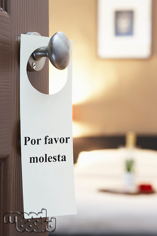 Sign with Spanish text hanging on hotel room door