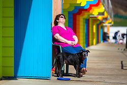 © Licensed to London News Pictures. 18/04/2018. Scarborough UK. A lady sunbathes outside her beach hut on Scarborough beach this morning as the country prepares for more warm weather. Photo credit: Andrew McCaren/LNP