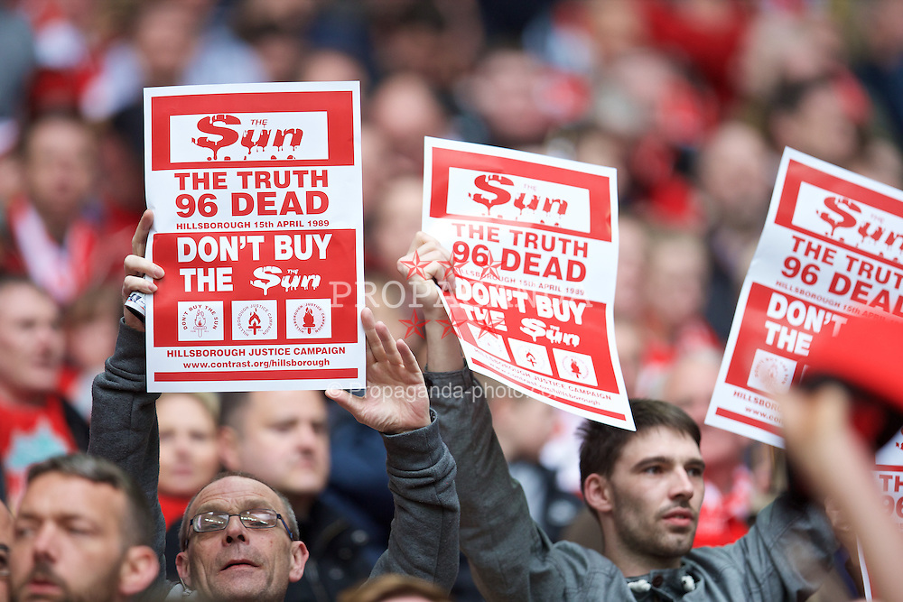 LONDON, ENGLAND - Sunday, April 19, 2015: A Liverpool supporter holds up a 'Don't Buy The Sun' poster before the FA Cup Semi-Final match against Aston Villa at Wembley Stadium. (Pic by David Rawcliffe/Propaganda)