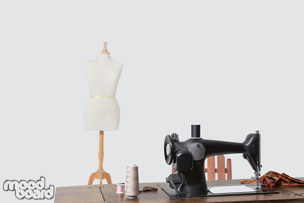 Mannequin and sewing machine with threads over gray background