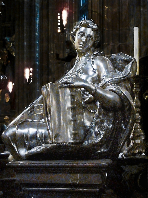 Silver and silver-gilt sculpture on the tomb of St John of Nepomuk in the Cathedral of St Vitus, Prague.  a Baroque monument cast in silver and silver-gilt that was designed by Fischer von Erlach, 1736.  Detail of a seated female figure holding a large book upright with her left hand and looking mournfully over he shoulder.