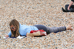 © Licensed to London News Pictures. 08/07/2014. Brighton, UK. A woman reading on Brighton beach.Despite temperatures in the next weeks are expected to soar to 86F around the UK with the South Coast predicted to hit record according to the MET the weather is very much cloudy today July 9th. Photo credit : Hugo Michiels/LNP