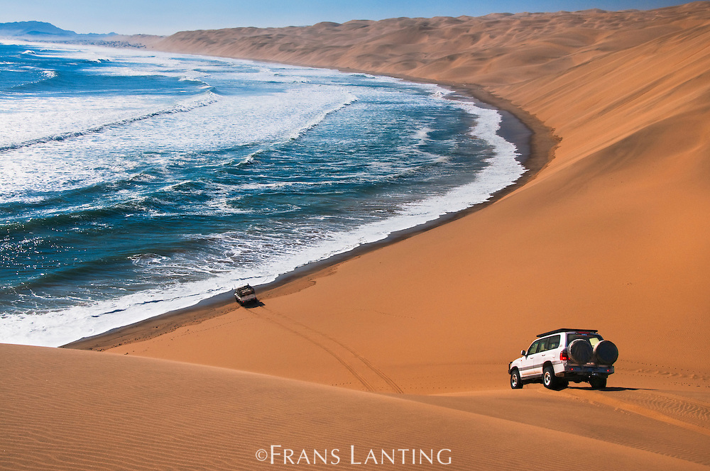 Off-road vehicles descending steep sand dunes to coast, Namib-Naukluft National Park, Namibia