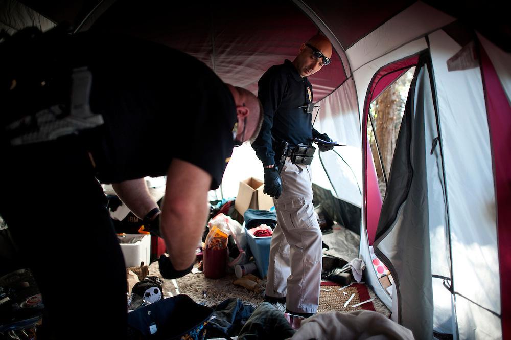 Savannah's Homeless Liaison Officer Tom Gentner interviews a suspected felon near the  camps under the Talmadge Memorial Bridge overpass Tuesday, Jan. 21, 2014, in Savannah, Ga. (© Photo/Stephen Morton)