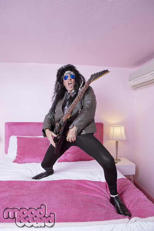 Full-length of hippie musician playing guitar